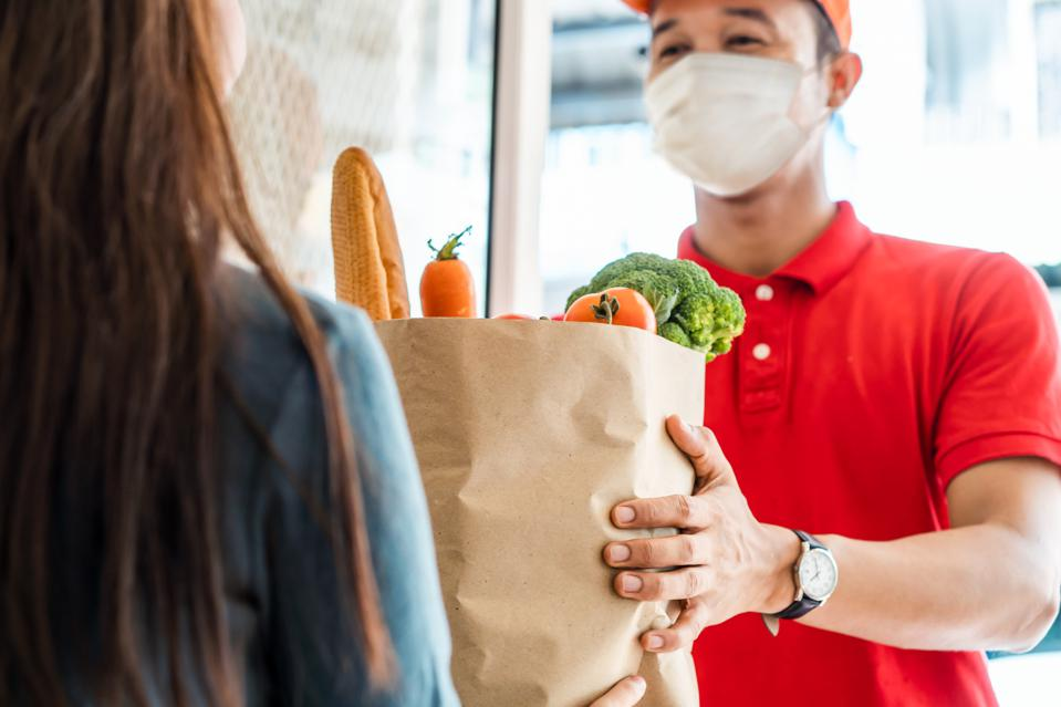A delivery person brings groceries during the pandemic.
