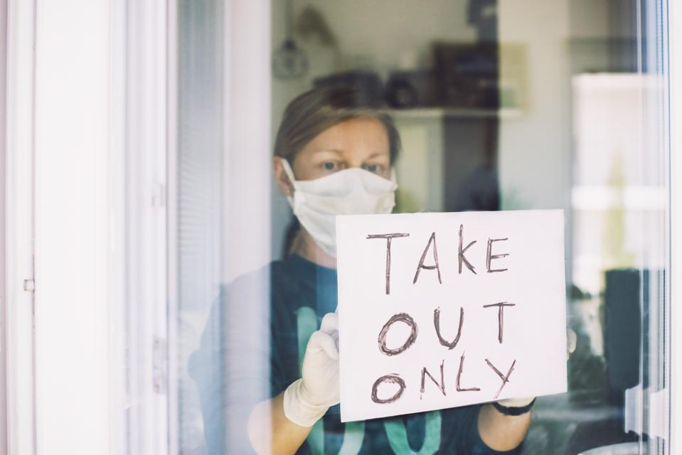 Woman put ″Take Out Only″ sign on front door shop