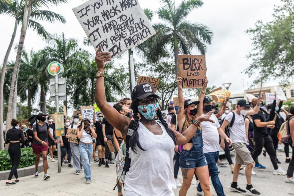 Protesters march through the streets of Miami protesting...