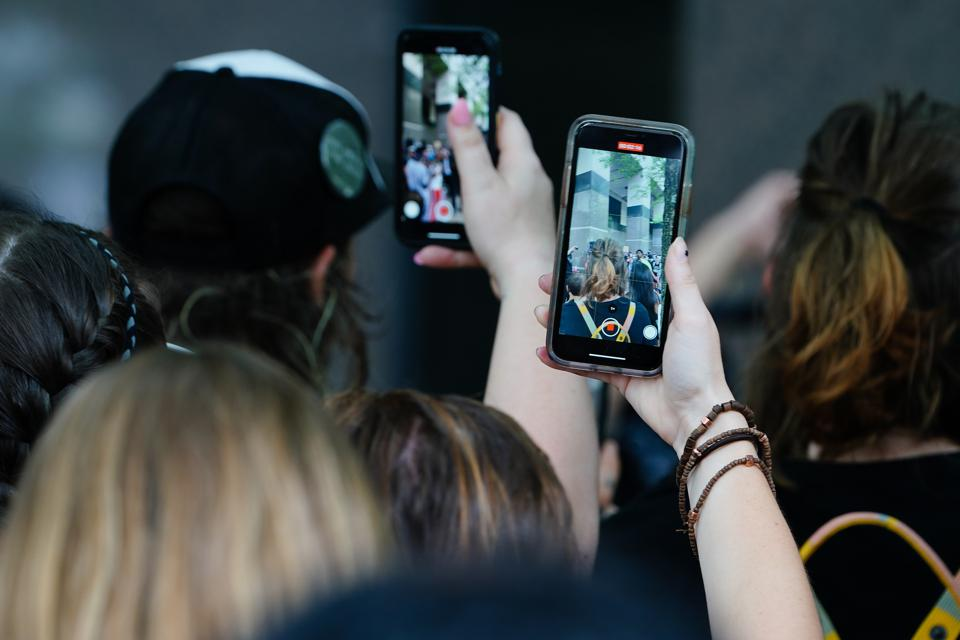 People using phones to record a speaker during a protest against police brutality.