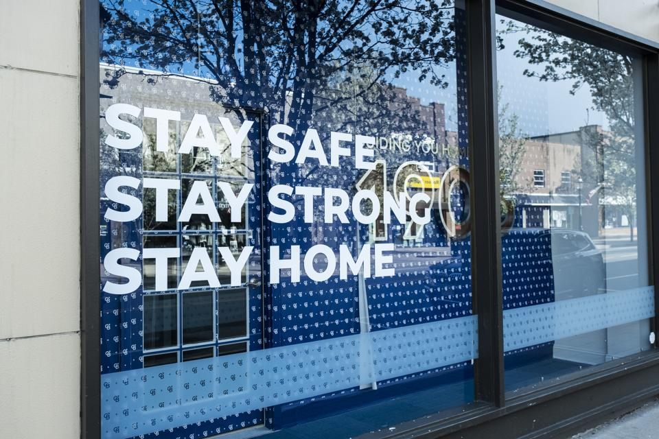 A sign in a window states, ″Stay Safe, Stay Strong, Stay Home.″