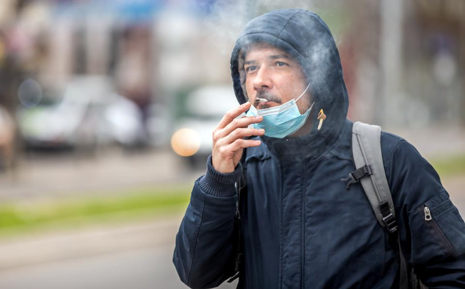 Man with mask during COVID-19 pandemic smoking.