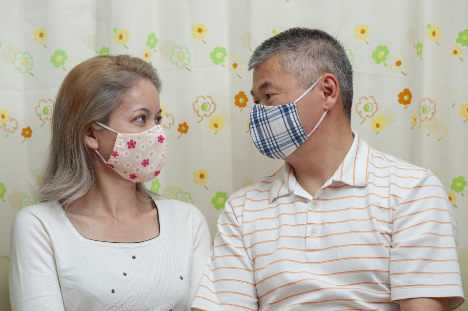 Couple wearing homemade face mask (DIY) for protection against coronavirus (COVID-19).