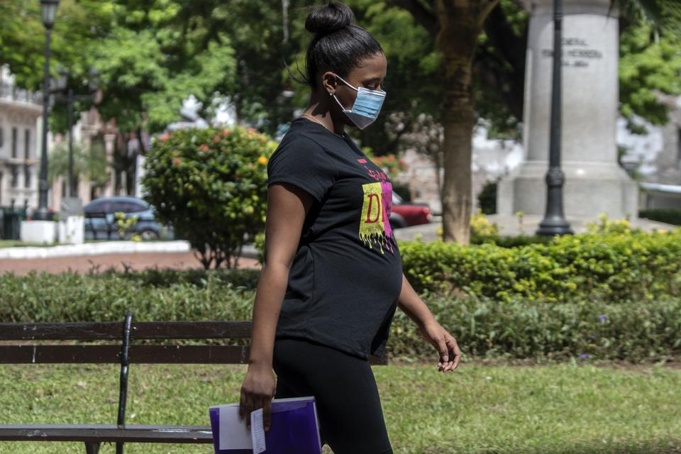 A pregnant woman wearing a blue face mask walking in a park.