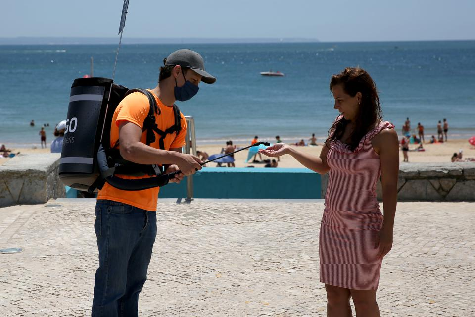 Man distributes hand sanitizing gel at a beach in Lisbon, Portugal, Europe