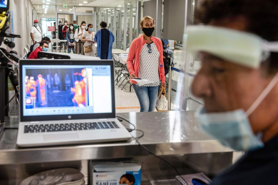 Man monitors temperatures of passengers arriving in Cyprus airport for Covid-19