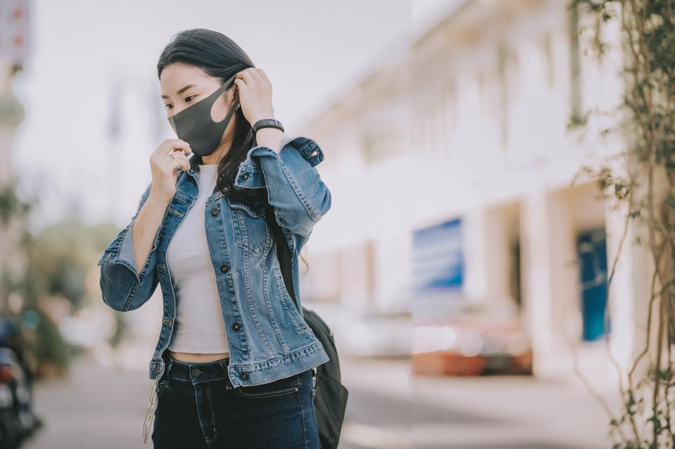 a young Asian Chinese girl tourist in penang, malaysia , south east Asia putting on mask