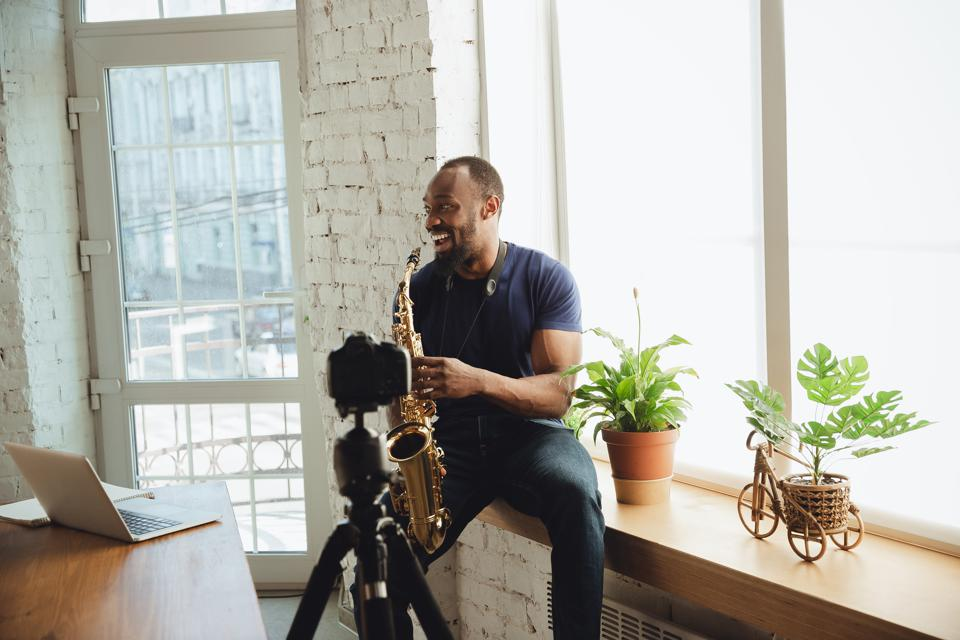 African-american musician playing saxophone during online concert at home isolated and quarantined, laughting
