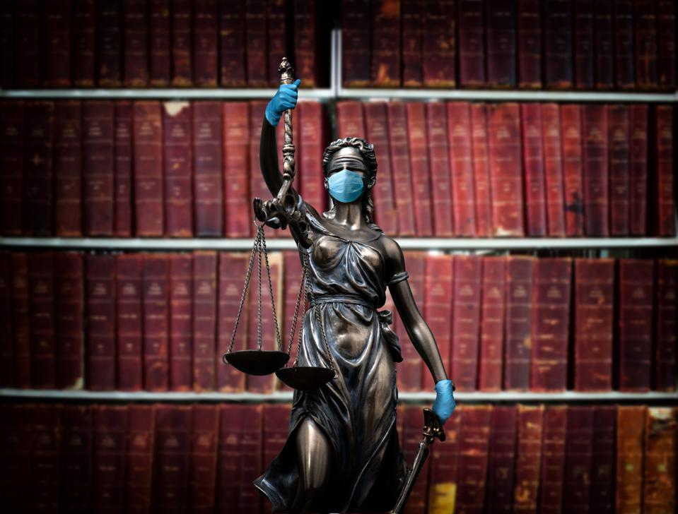 Lady justice wearing a medical mask and medical gloves.