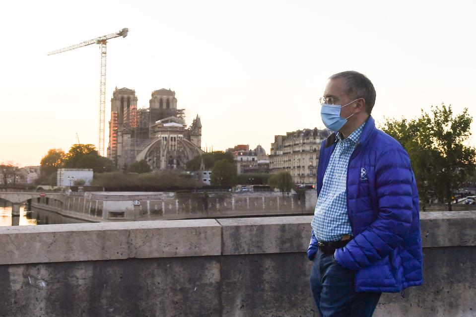 A man wearing a protective mask walks during the ring of the Bourdon bell to commemorate the first anniversary of the fire of the Notre-Dame Cathedral.