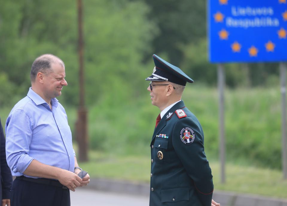 Lithuanian Prime Minister Saulius Skvernelis greets an officer as EU borders reopen