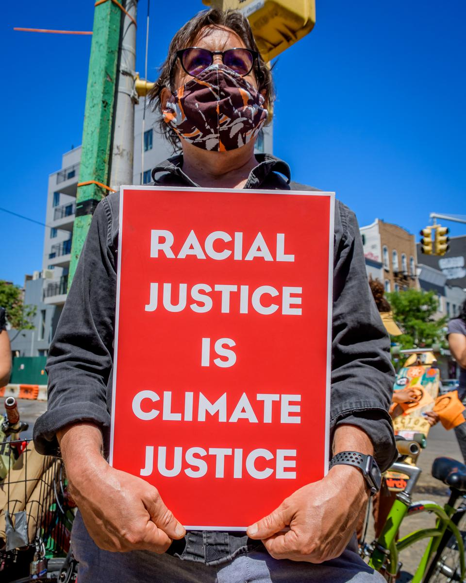 Protester holding a sign reading Racial Justice Is Climate...