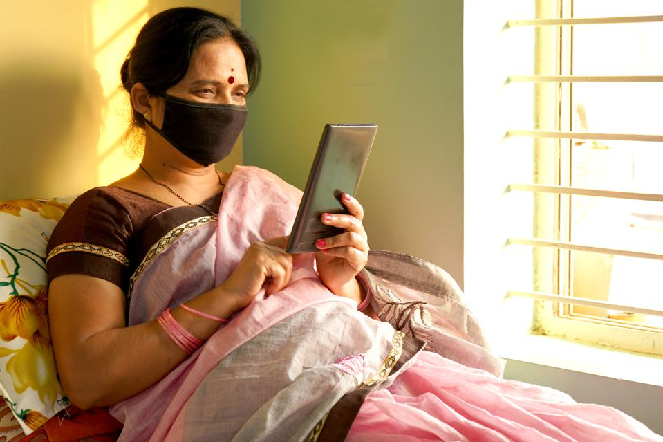 Indian woman with face protective mask reading news on a tablet at home in India.