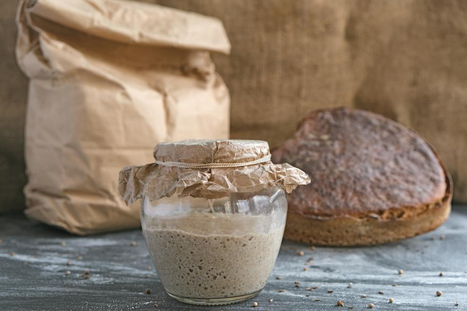 still life with sourdough in glass jar, rye bread in shape heart and paper bag with whole grain flour on table