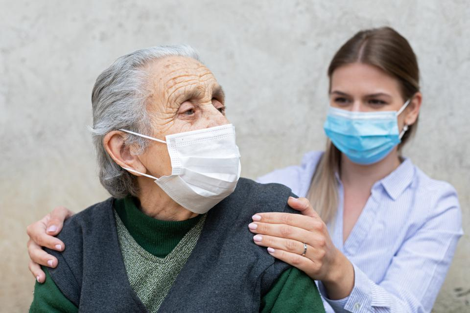 Caregiver with elderly ill woman wearing mask.