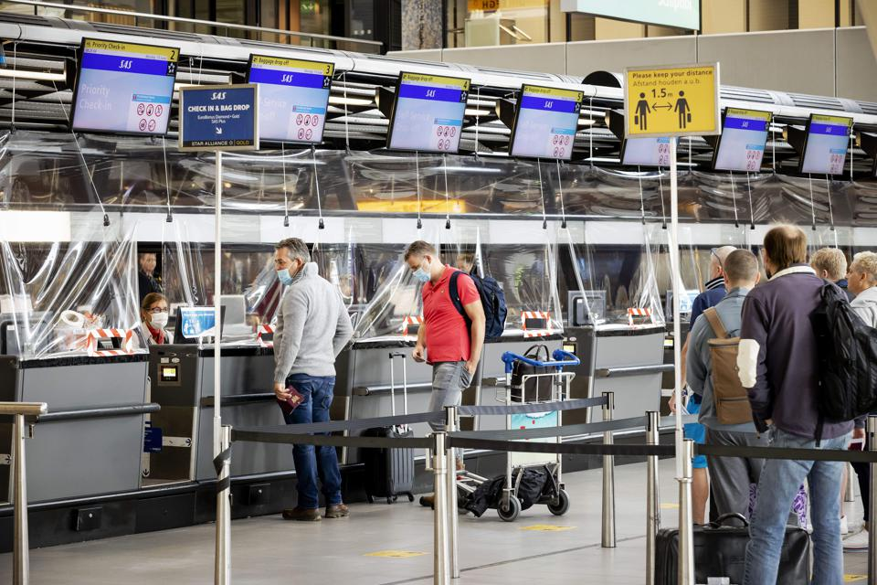 Passengers queue at check-in at Schiphol airport Amsterdam as EU travel ban ends