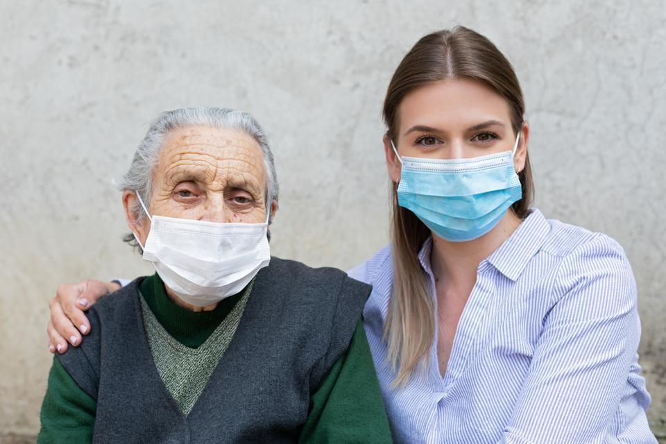Elderly ill woman and healthy caregiver wearing face masks to protect against coronavirus.