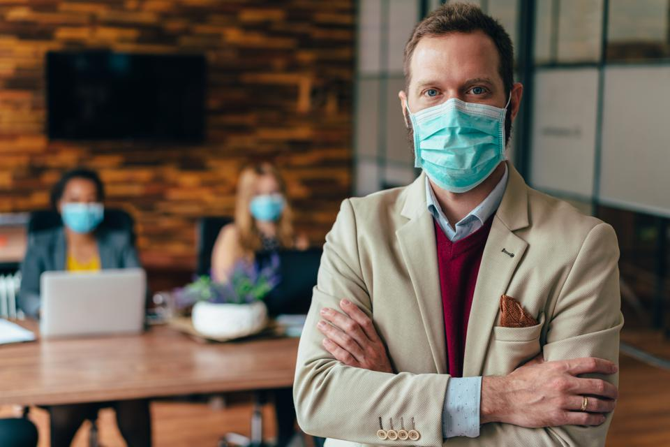 Businesspeople working with face masks in the office during a pandemic