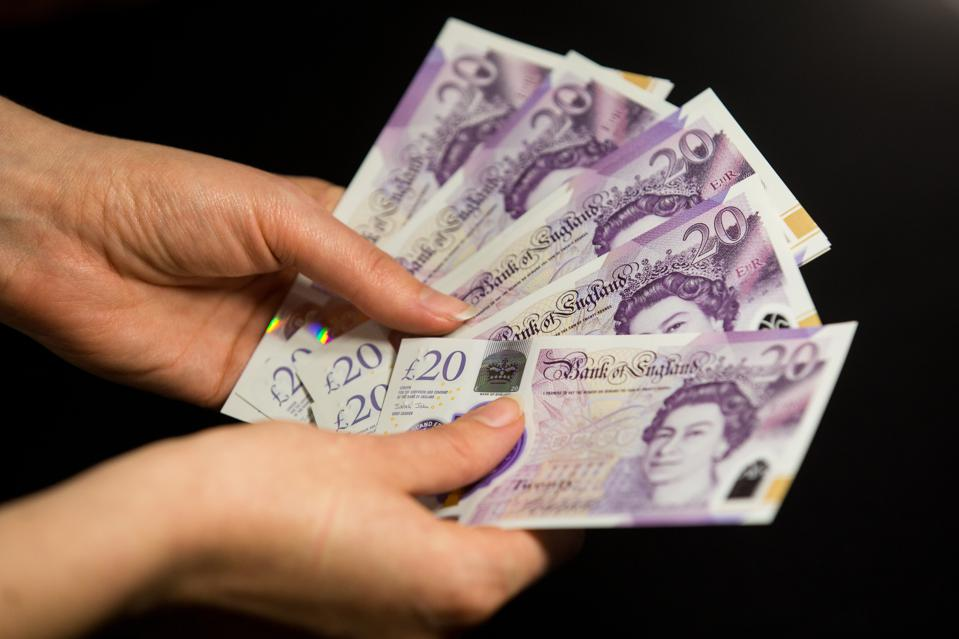In this photo illustration banknotes of the pound sterling,...