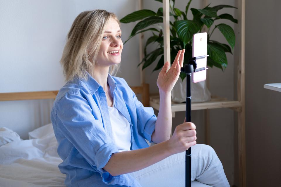 Woman blogger talking with followers, live streaming, looking to smartphone screen sitting on bed. Making video call to friends and parents. Social media, instagram, stay home and quarantine