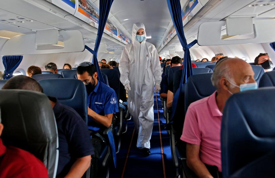 People on board plane in Israel with cabin crew in protective Covid clothing