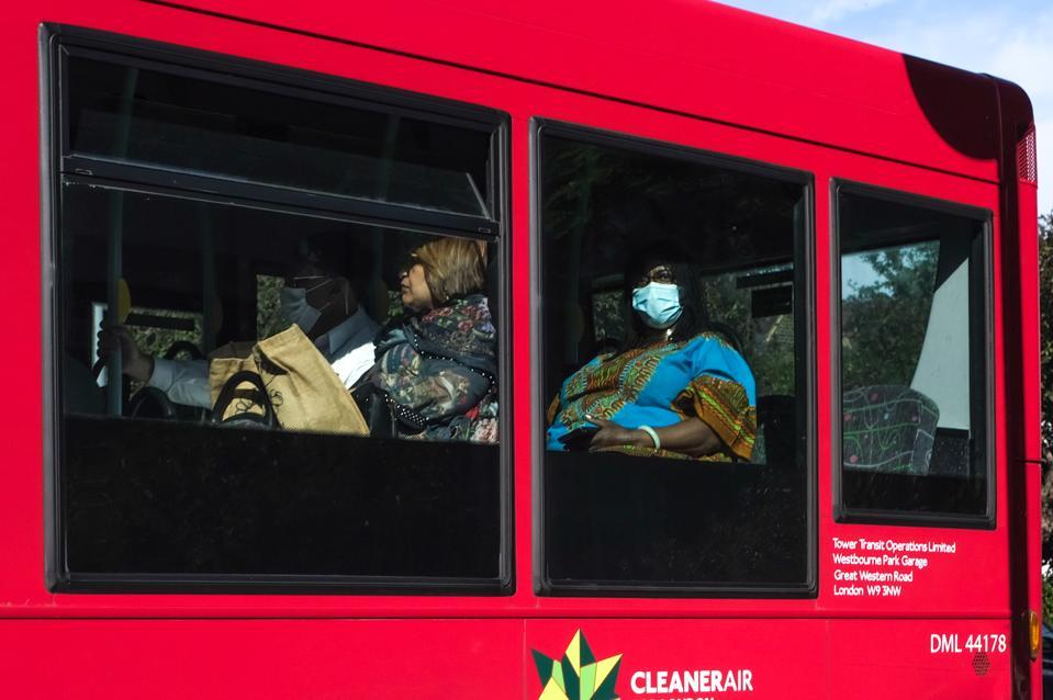 People passengers wearing masks on bus in London England UK