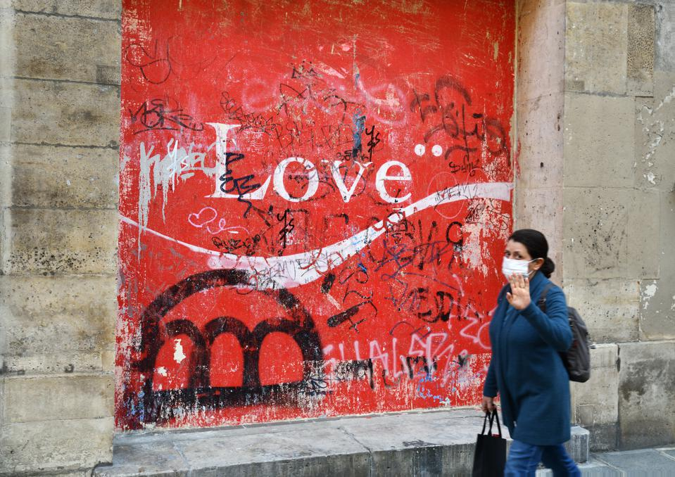 Woman walks past love sign in paris wearing covid-19 mask