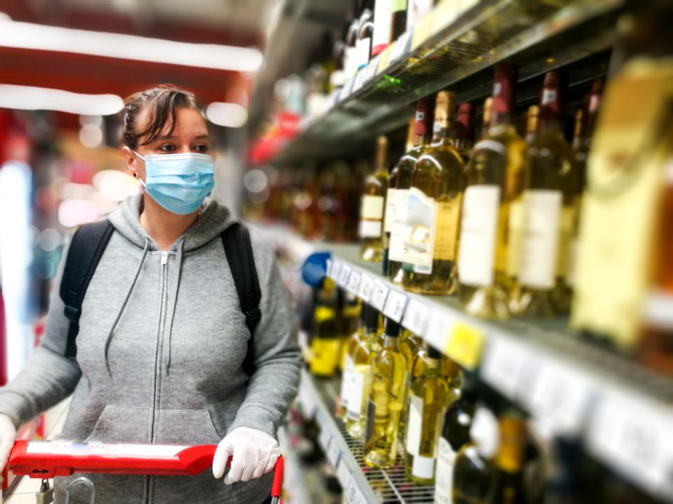 A Woman Wearing a Protective Mask and Gloves to Shop for Wine