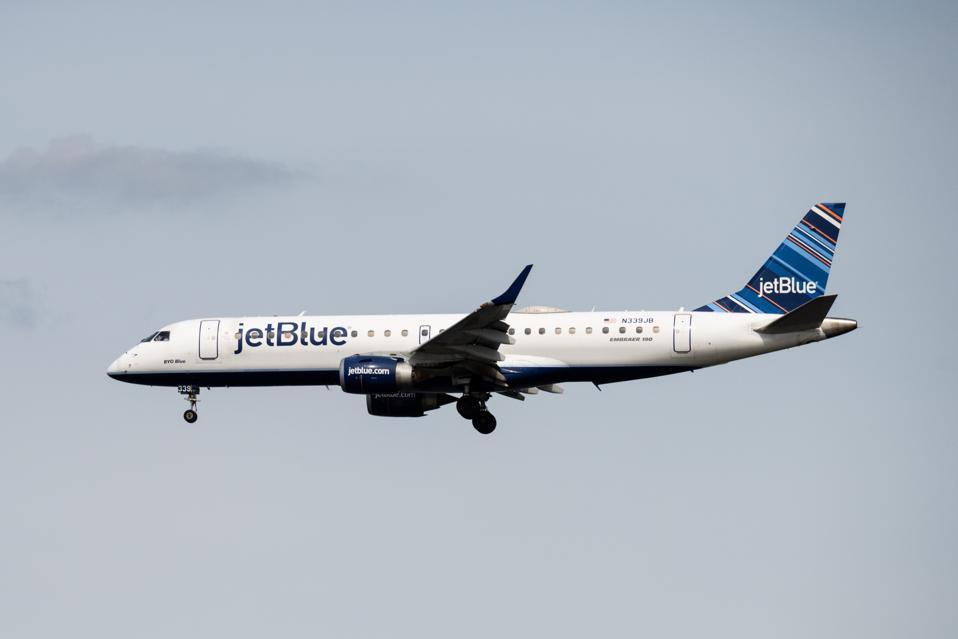 A JetBlue Airways Embraer E190AR landing at Ronald Reagan...