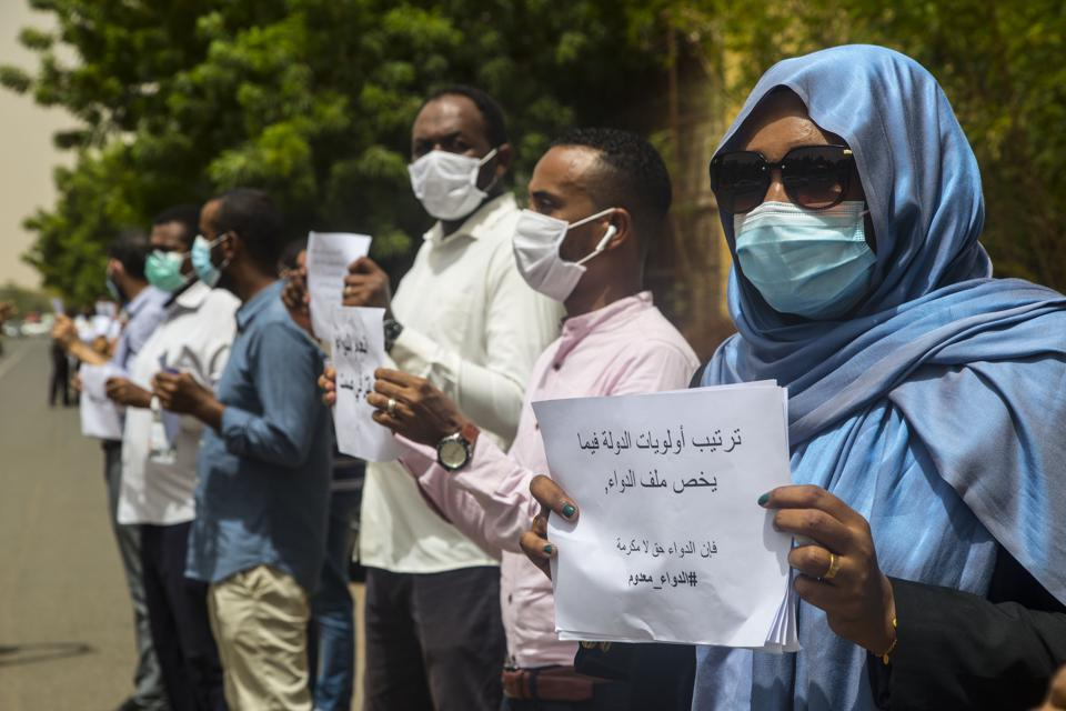 People in a line wearing masks and holding up signs in Arabic