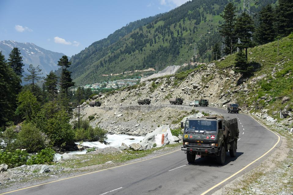 Indian army convoy moves along the national Highway leading...