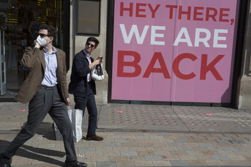 Shoppers in London pass a pink store sign reading ″Hey there, we are back.″