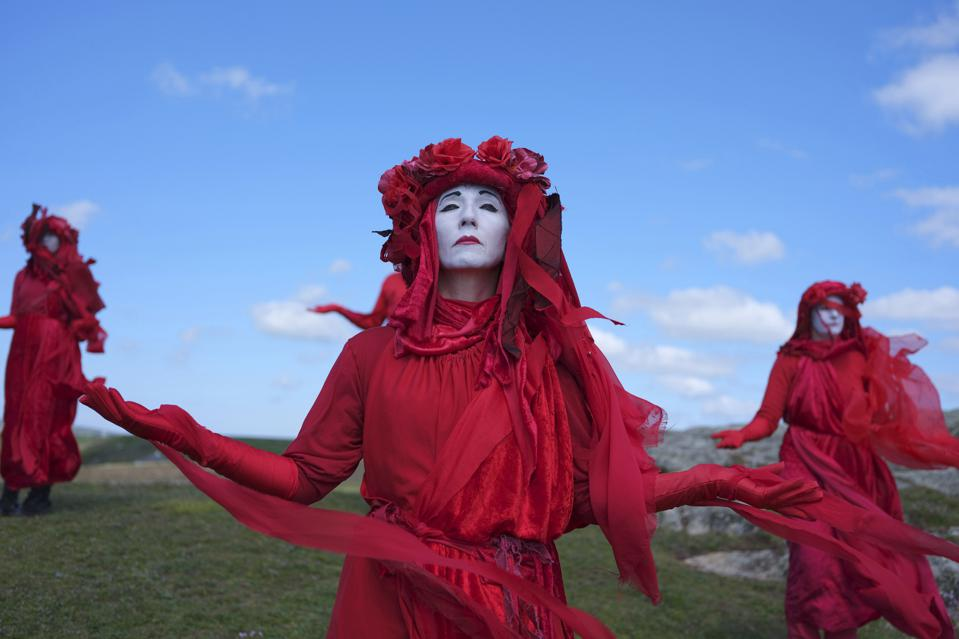 The spectacularly dressed Red Rebel protest group dance atop a sea cliff in Cornwall, U.K.