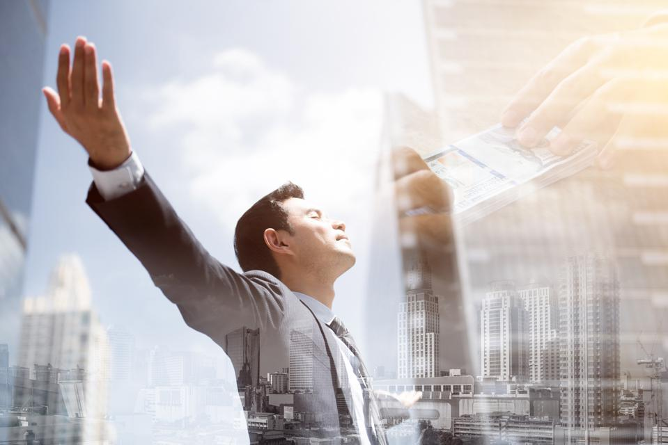 Success businessman in the city raising his arms, open palms, with face looking up