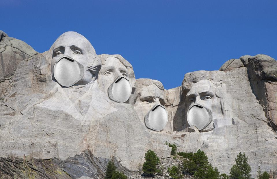 View of the carved sculptures of presidents on Mount Rushmore wearing the face masks.