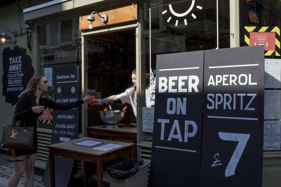A customer orders a drink from a re-opened bar in Soho where beer on tap is available.