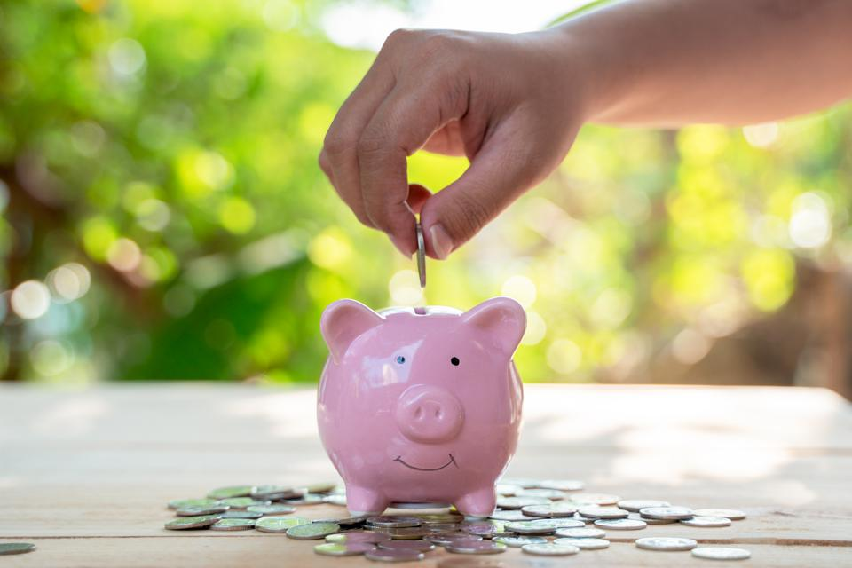 Piggy bank with hand inserting coin money, on green tree background, saving and finance concept.