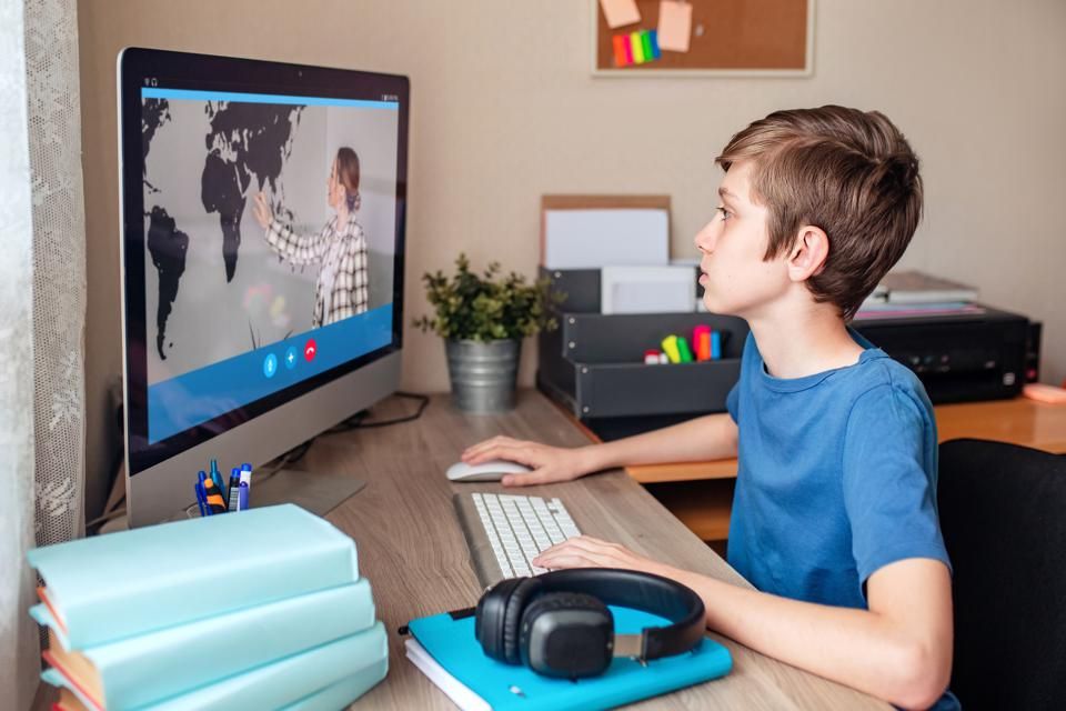Boy video conferences with a tutor on the computer at home.