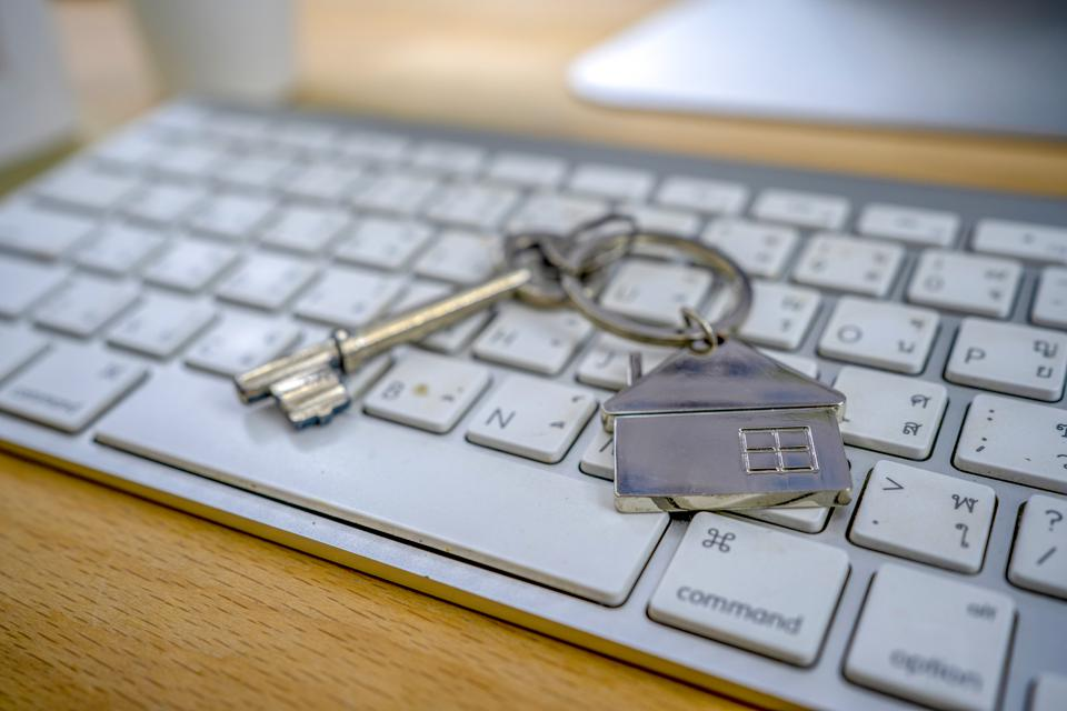 Mortgage concept with key and house-shaped keyring on laptop keyboard.