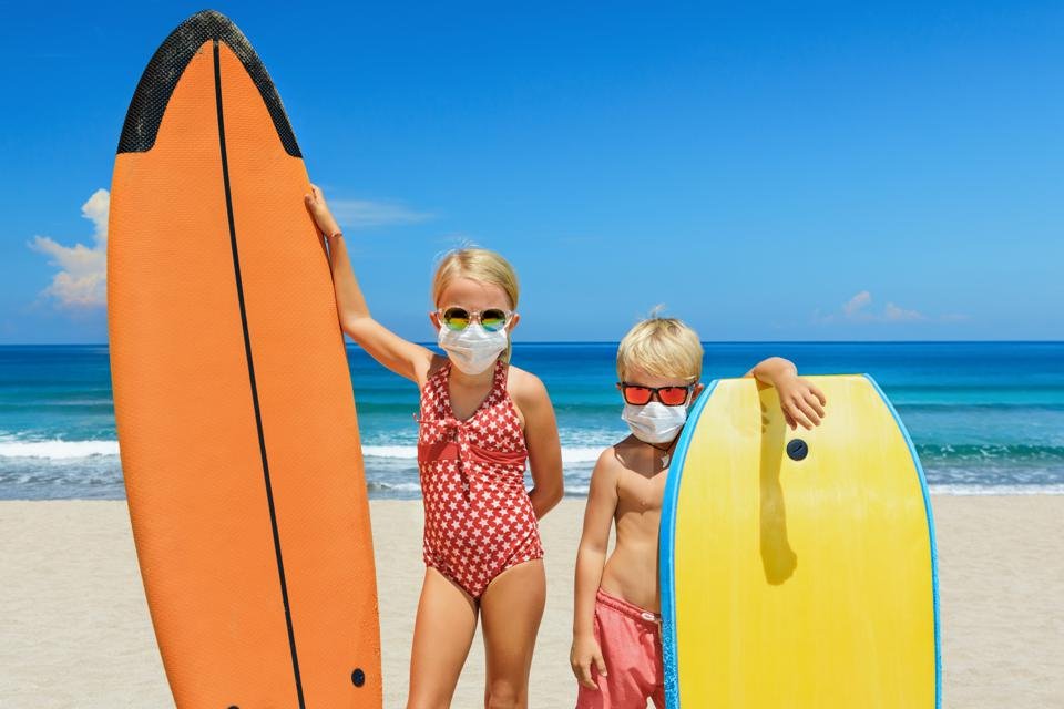 Young surfers wearing sunglasses, protective mask on sea beach