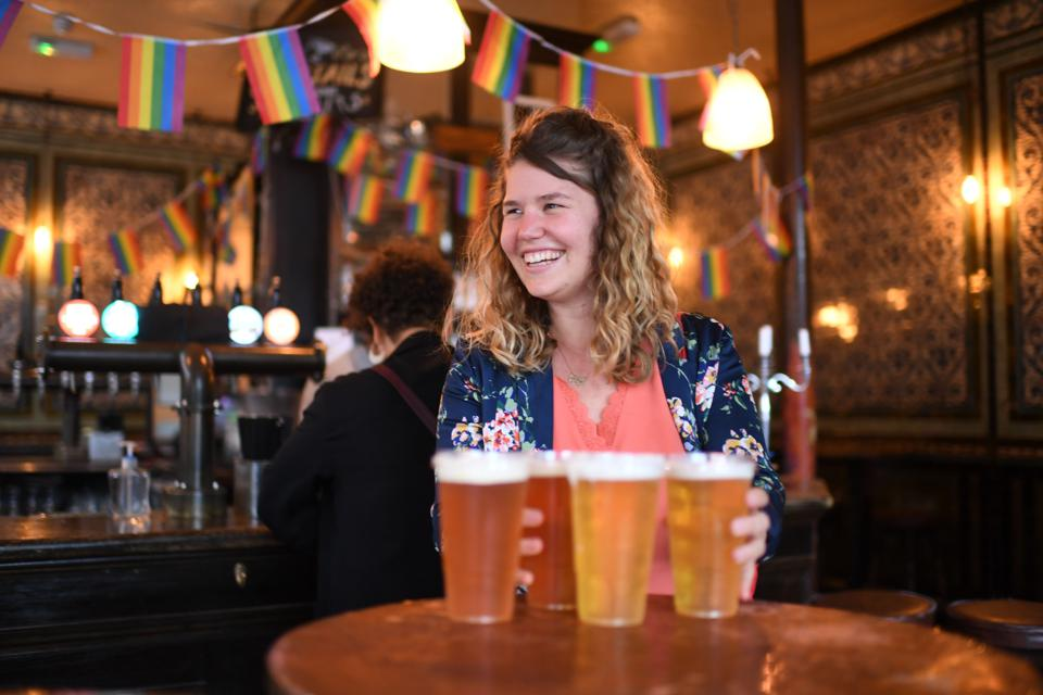 Customers leave with pints of beer for takeaway at The Ten Bells pub in east London on June 27, 2020.