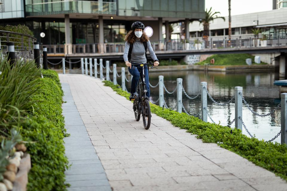 Woman wearing a protective mask and a cycling helmet in the streets, biking in the streets
