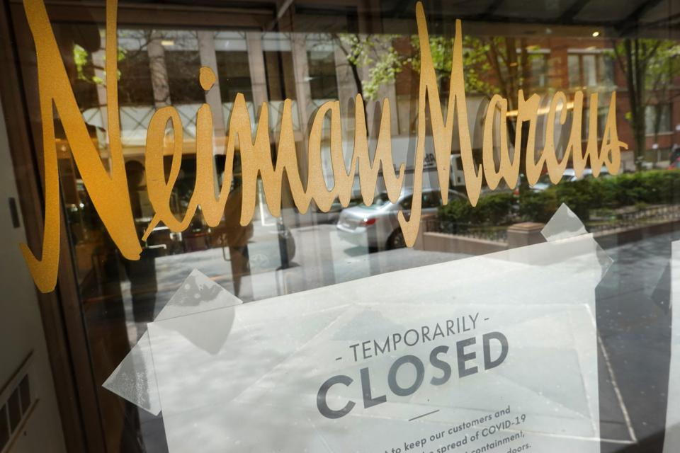 A window of a Neiman Marcus in Chicago, IL that has been shuttered shows a closed sign.