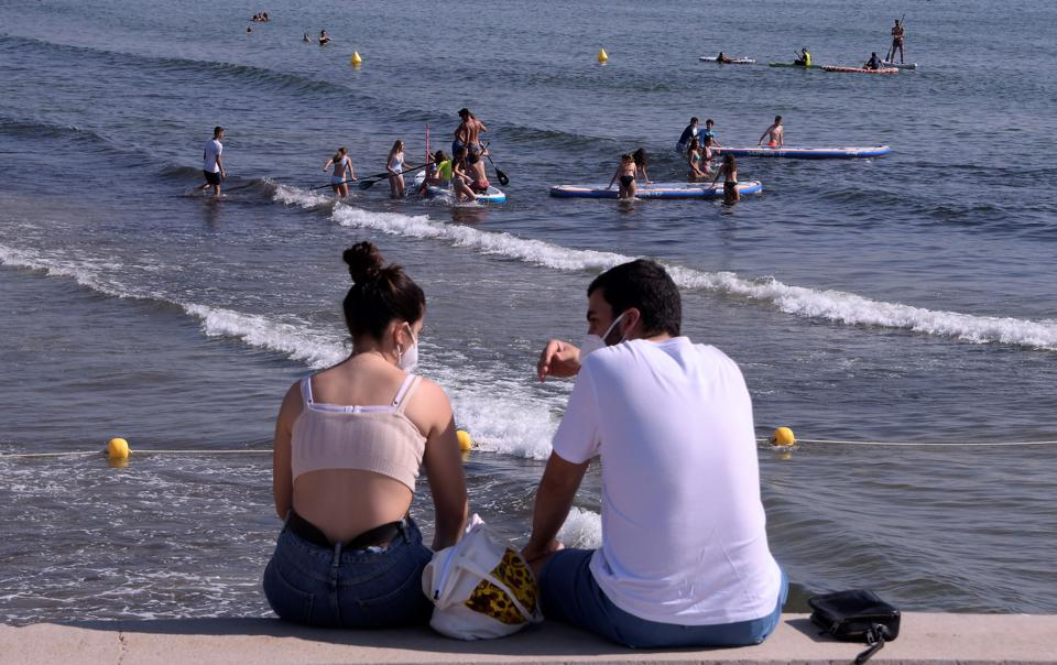 People with masks on beach in Spain, Europe, as summer tourism starts without US tourists