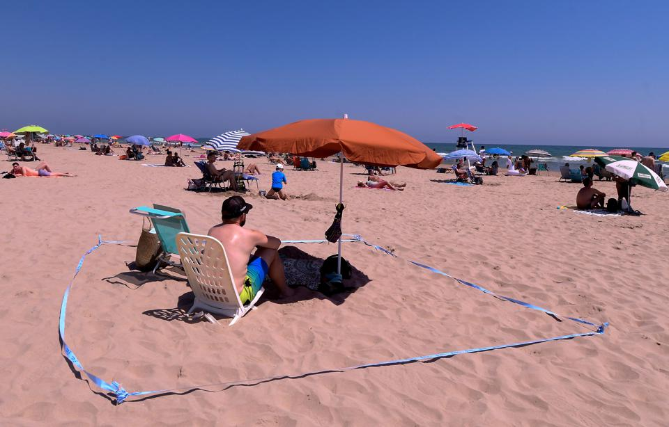 A man sunbathes on Spanish beach surrounded by a barrier tape as EU tourism restarts