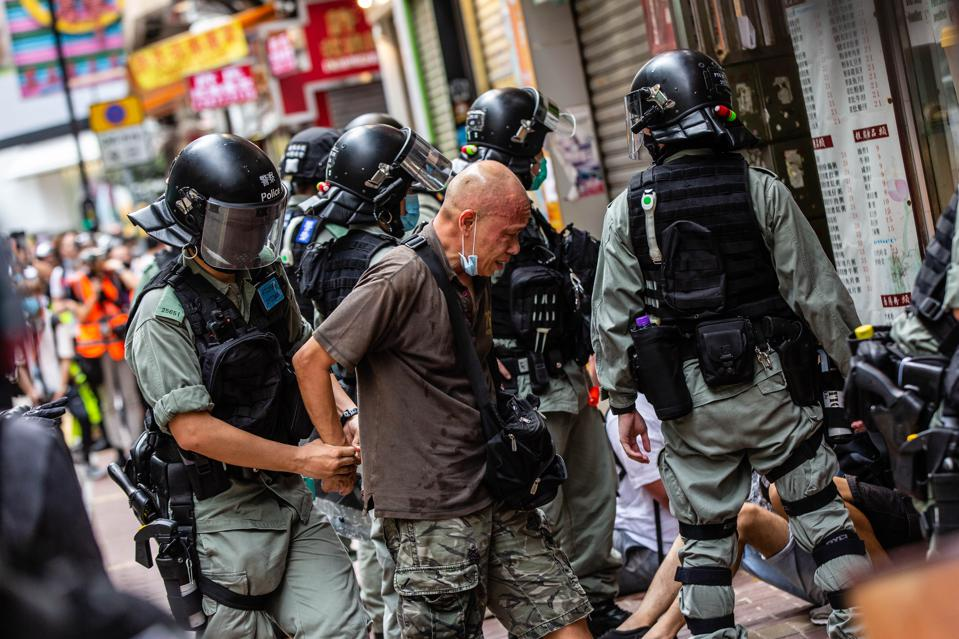 Riot police officers arresting a protester during the...