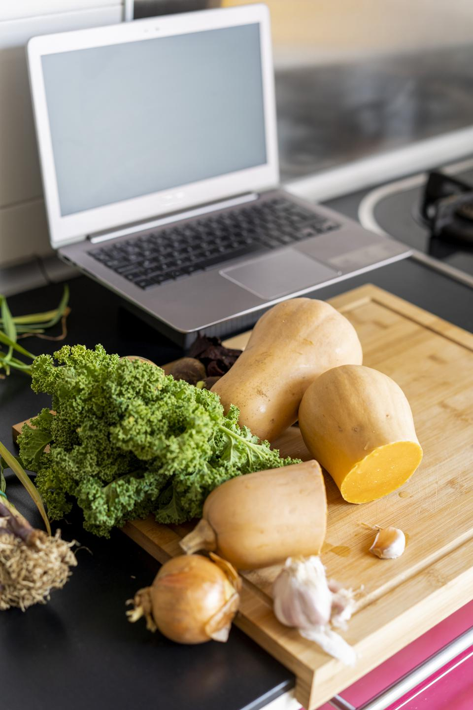 Healthy vegetables in kitchen with laptop