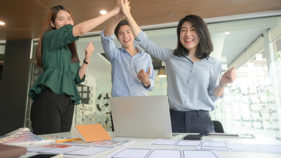 Cheerful Business People Doing High-Five In Office