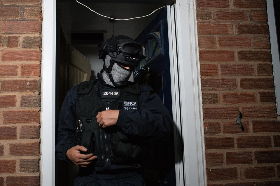 A police officer is seen raiding a property, in full protective gear