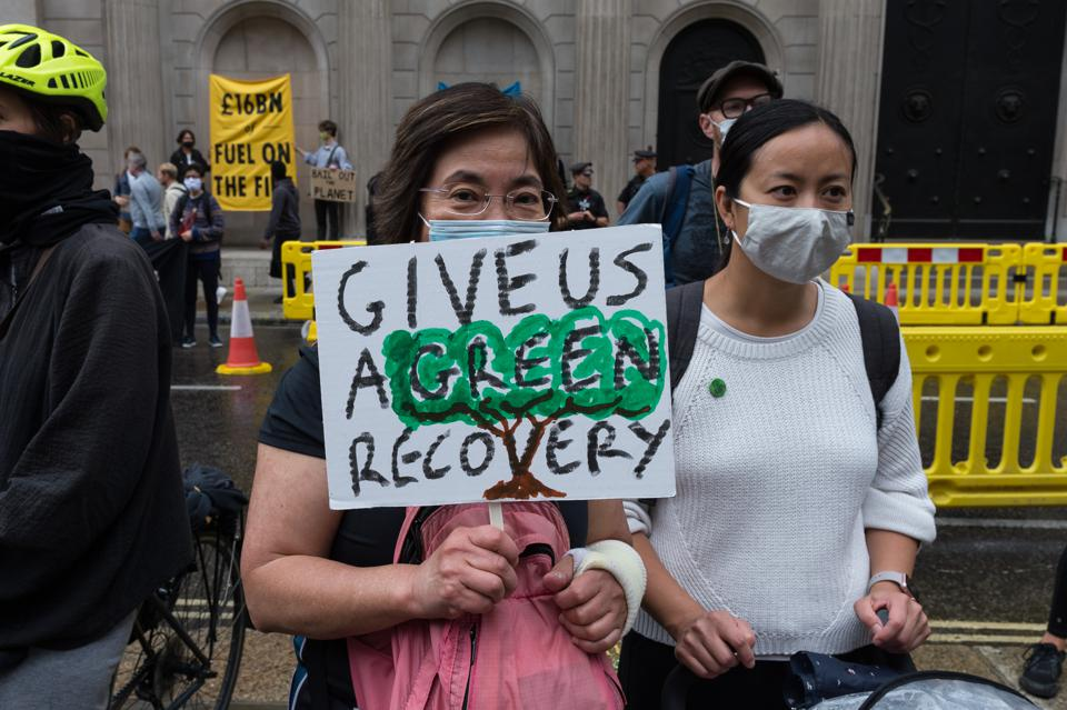A woman wearing a mask holds a sign saying ″Give us a green recovery.″
